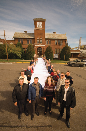 Flambeau River Papers employees and supporters celebrate the mill reopening by unfurling a roll in front its 78-year-old headquarters.