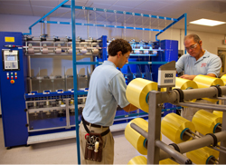 Technicians Sean Sommers (left) and Ed Young prepare DuPont Kevlar yarn for a quality test to ensure specifications are met.