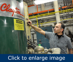 Figure 1. Technician adjusts the PLC controls on a Clayton Industries boiler.